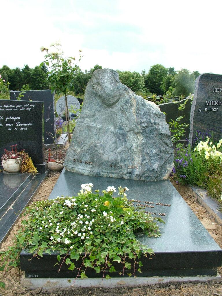 Zwarte grafsteen met grote zwerfkei